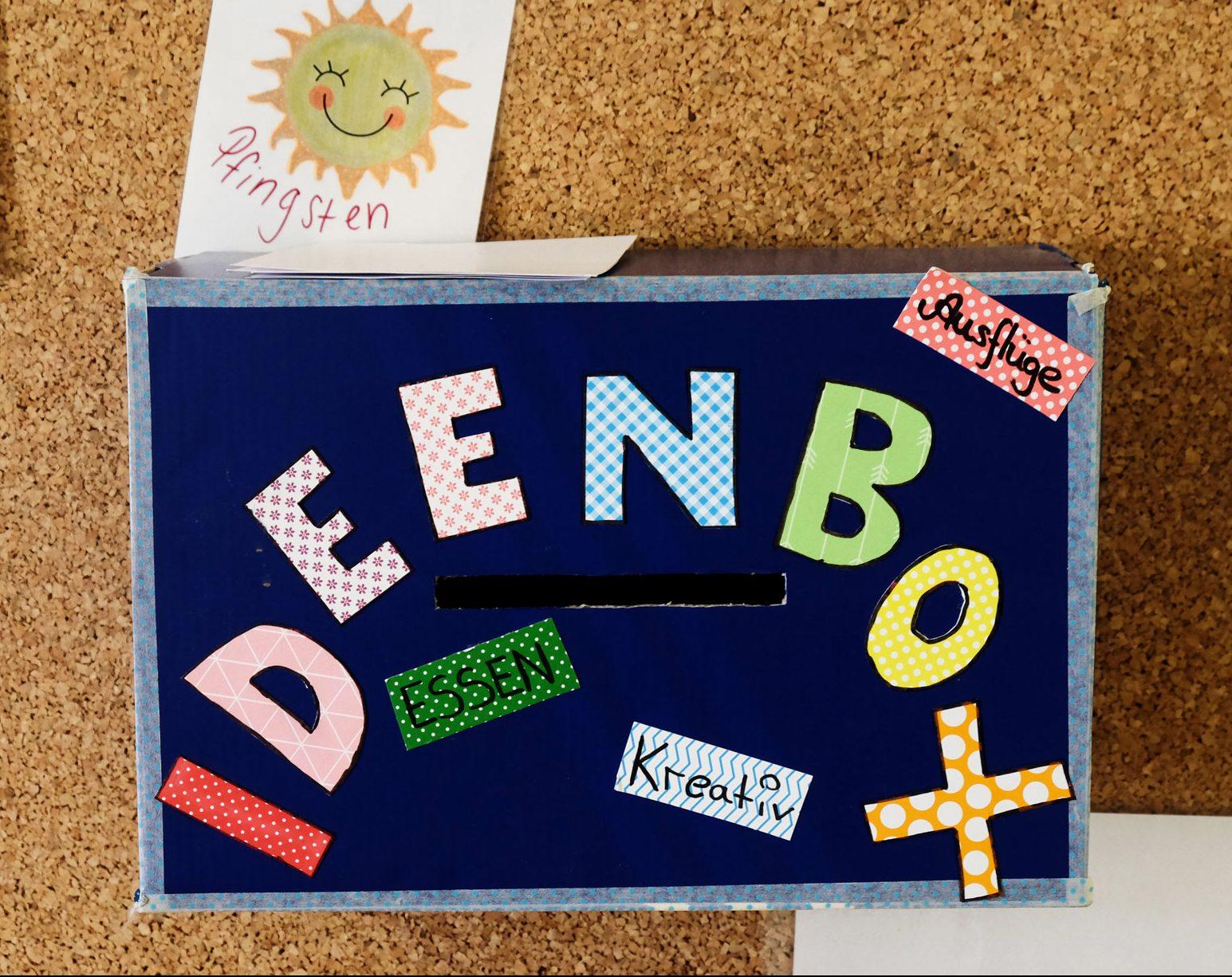 Blaue Ideenbox mit bunten Buchstaben vor einer Korkwand