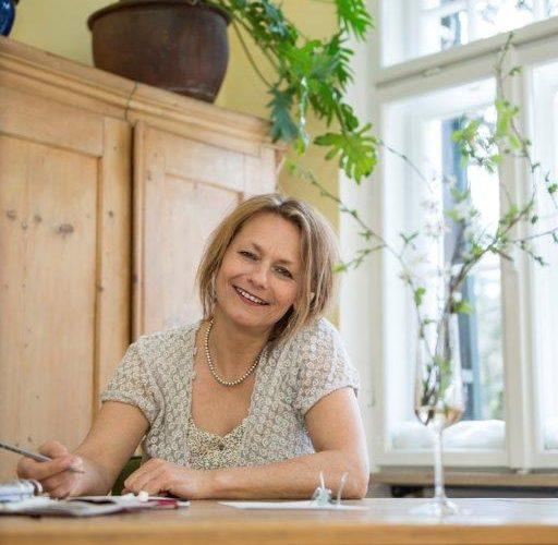 Sozialpädadogin Miriam M'Bengue sitzt lächelnd hinter einem Schreibtisch