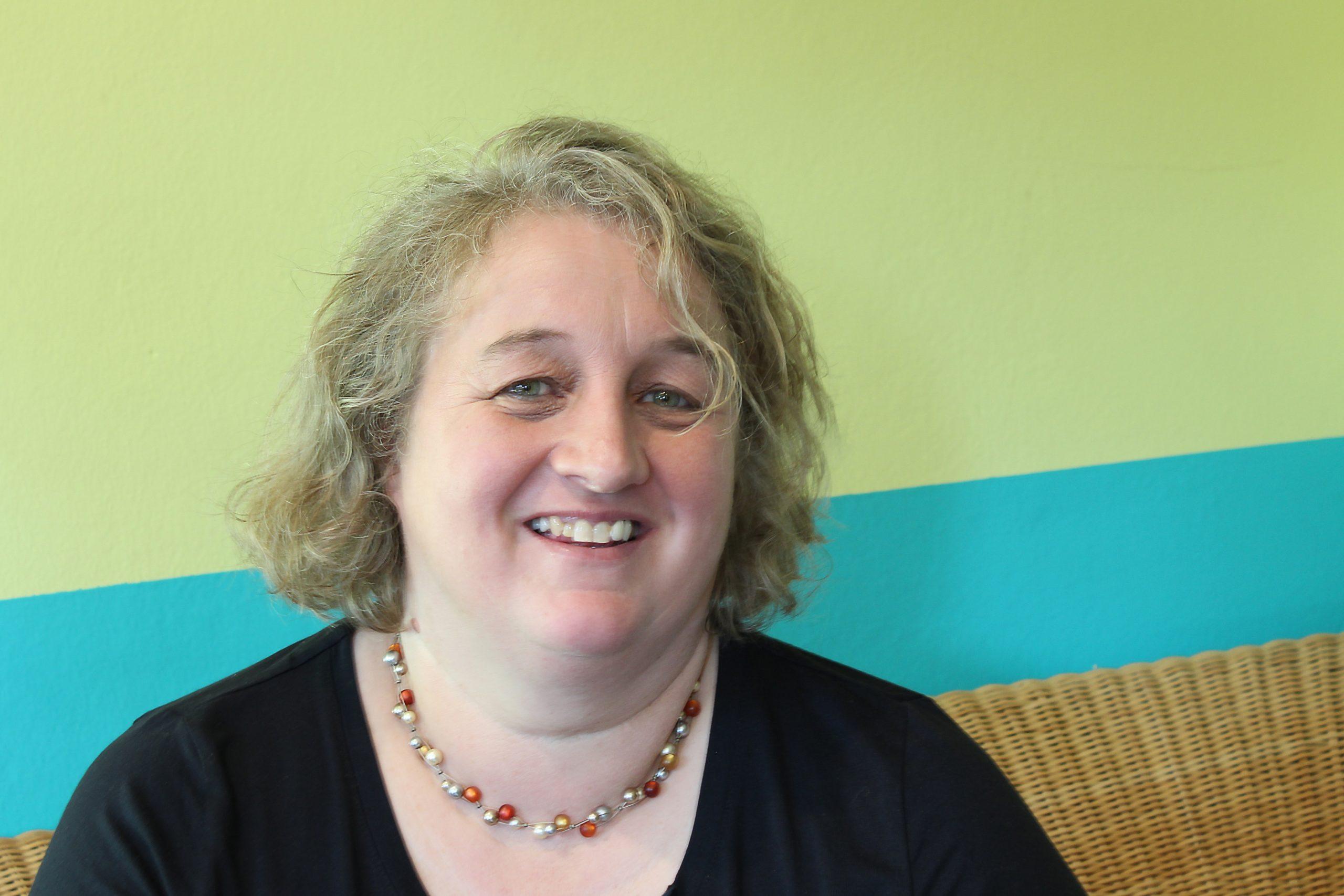 Rosemarie Pösl sitzt lächelnd auf einem Stuhl