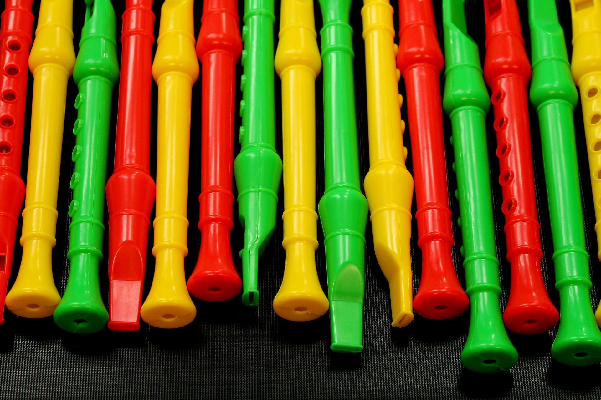 gelbe rote und grüne Flöten liegen auf einer dunklen Unterlage