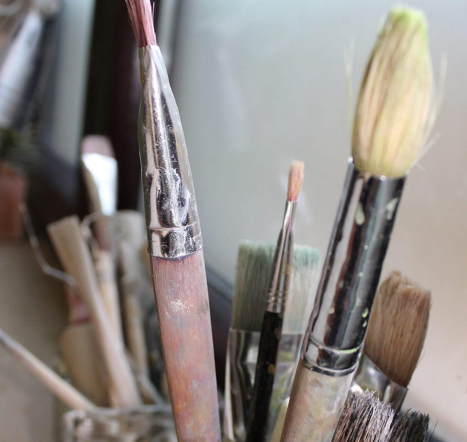 Nahaufnahme von Pinseln mit Holzgriffen, die in einem Becher aufrecht stehen