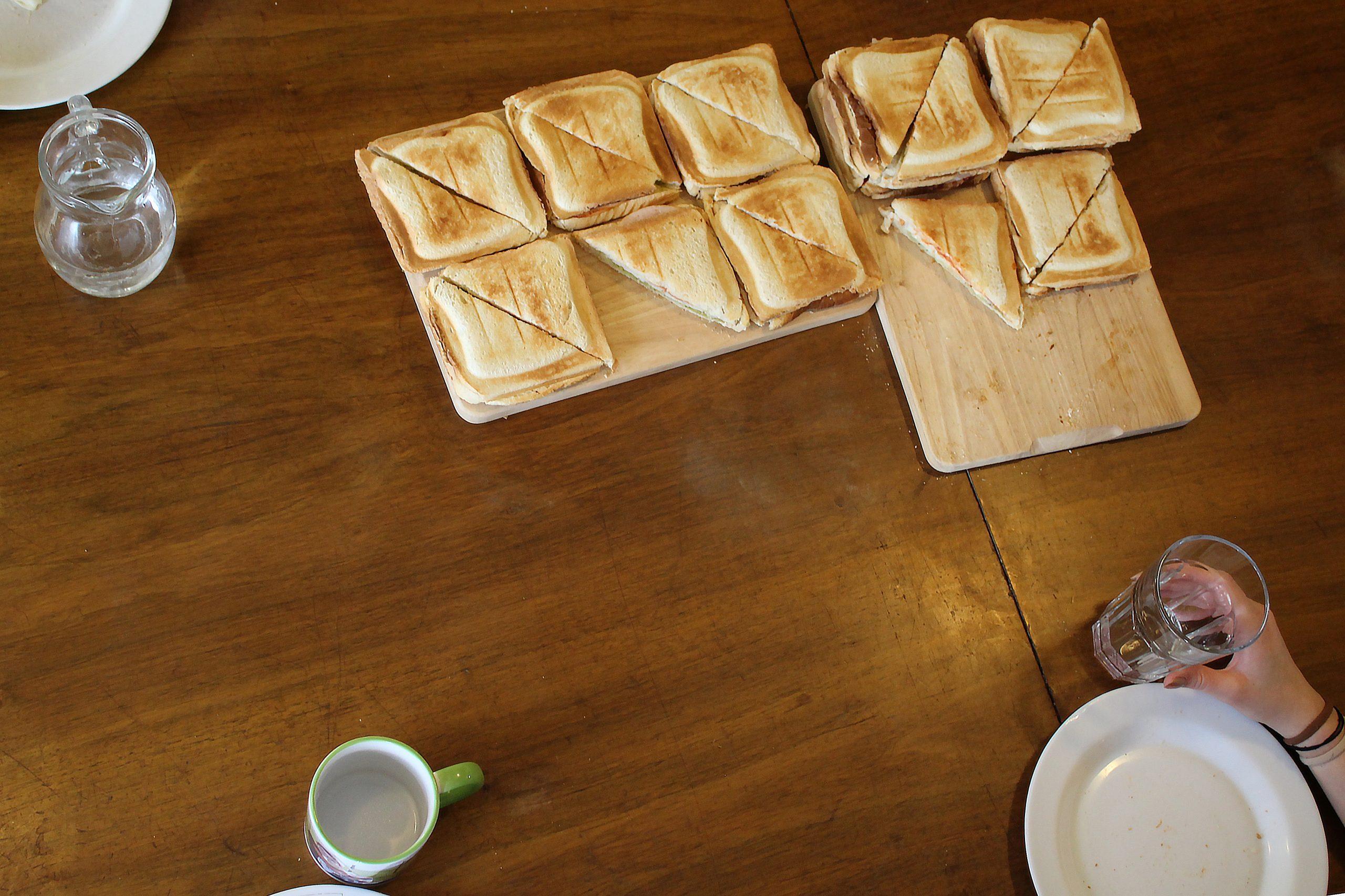 Sandwiches liegen auf zwei Holzplatten auf einem Tisch
