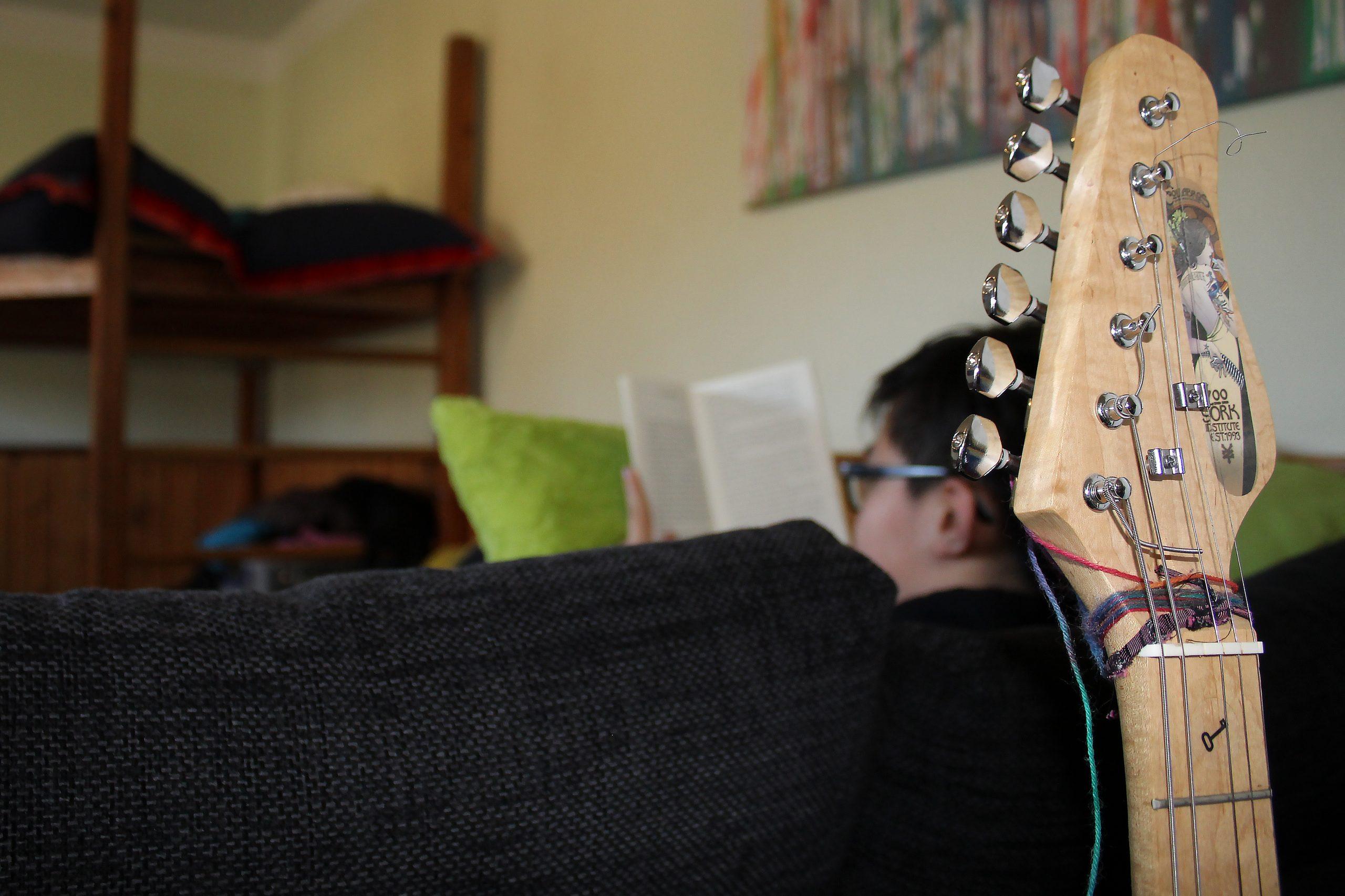 Eine Gitarre lehnt an einem Sofa, auf dem ein Junge sitzt und liest