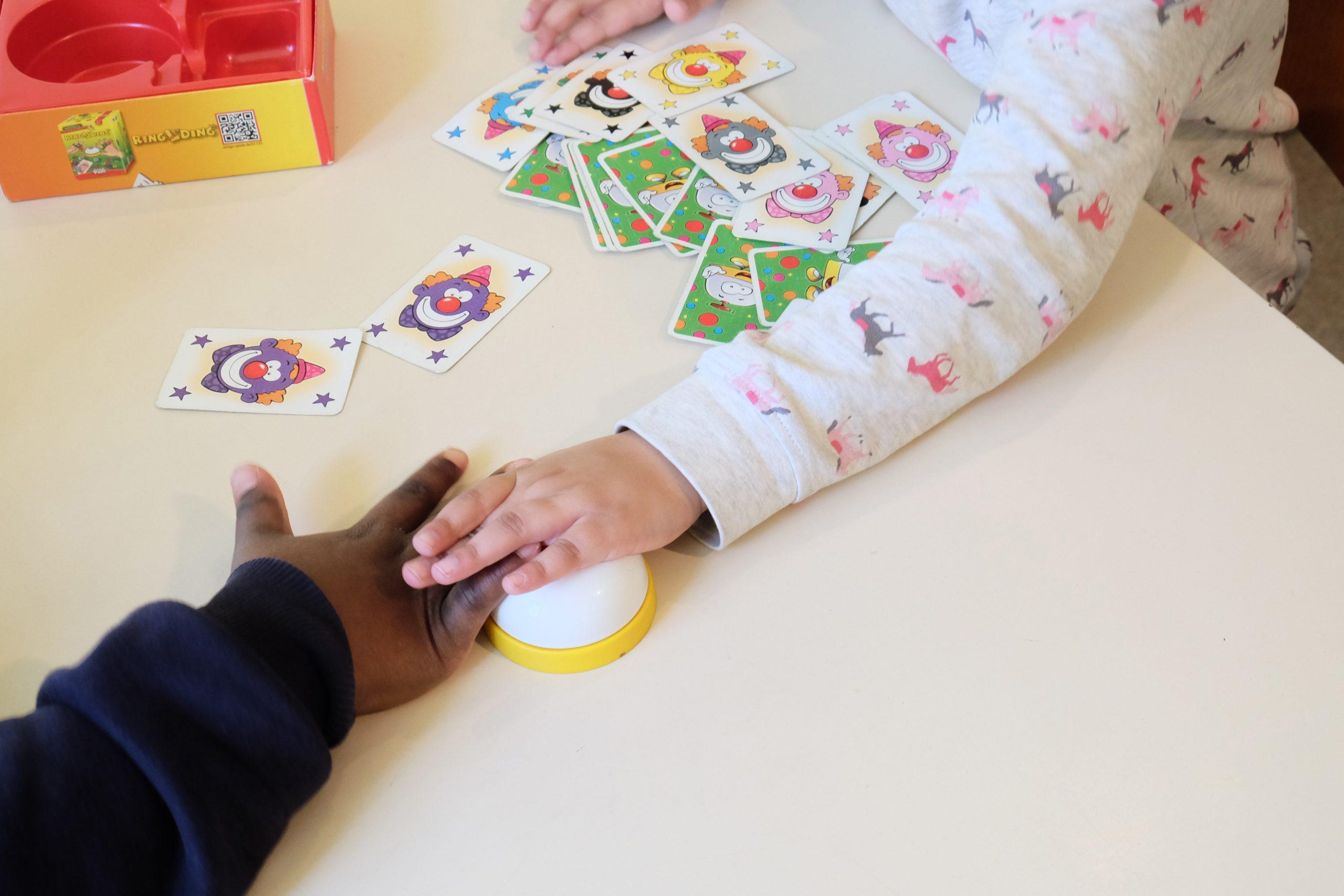 Kinder spielen ein Kartenpiel und schlagen auf eine Tischklingel