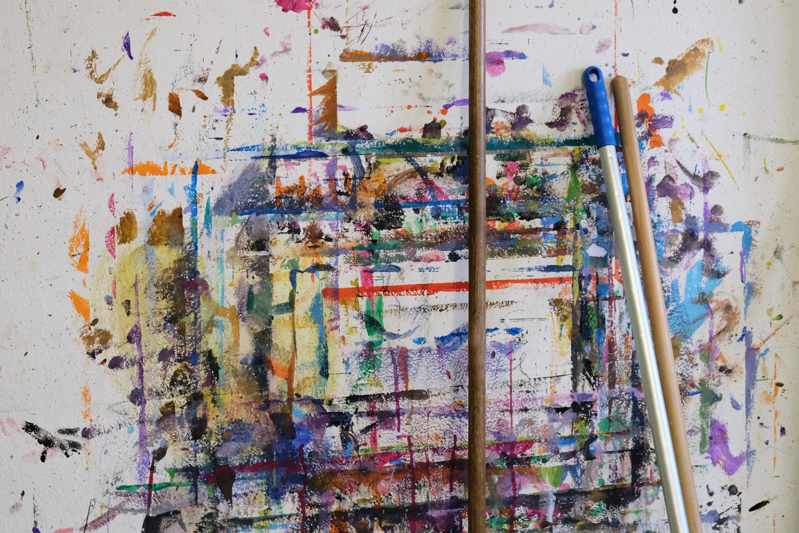 Wand mit bunten Farbklecksen und Besenstielen davor