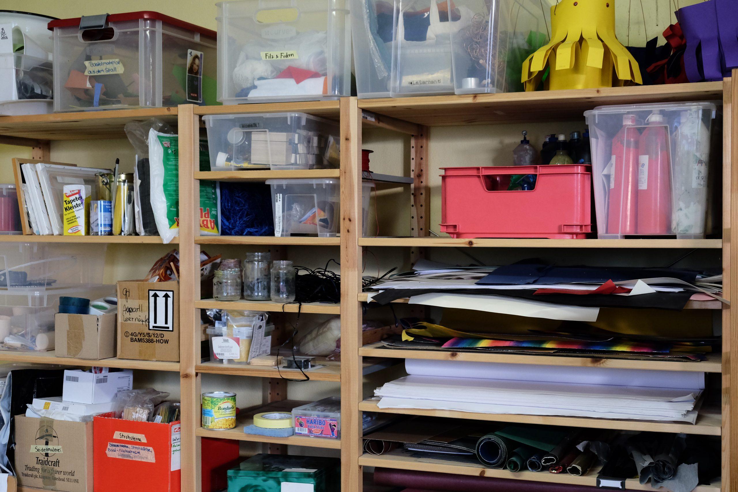 Holzregal befüllt mit Papier, Werkzeug, Bastel- und Mal-Utensilien
