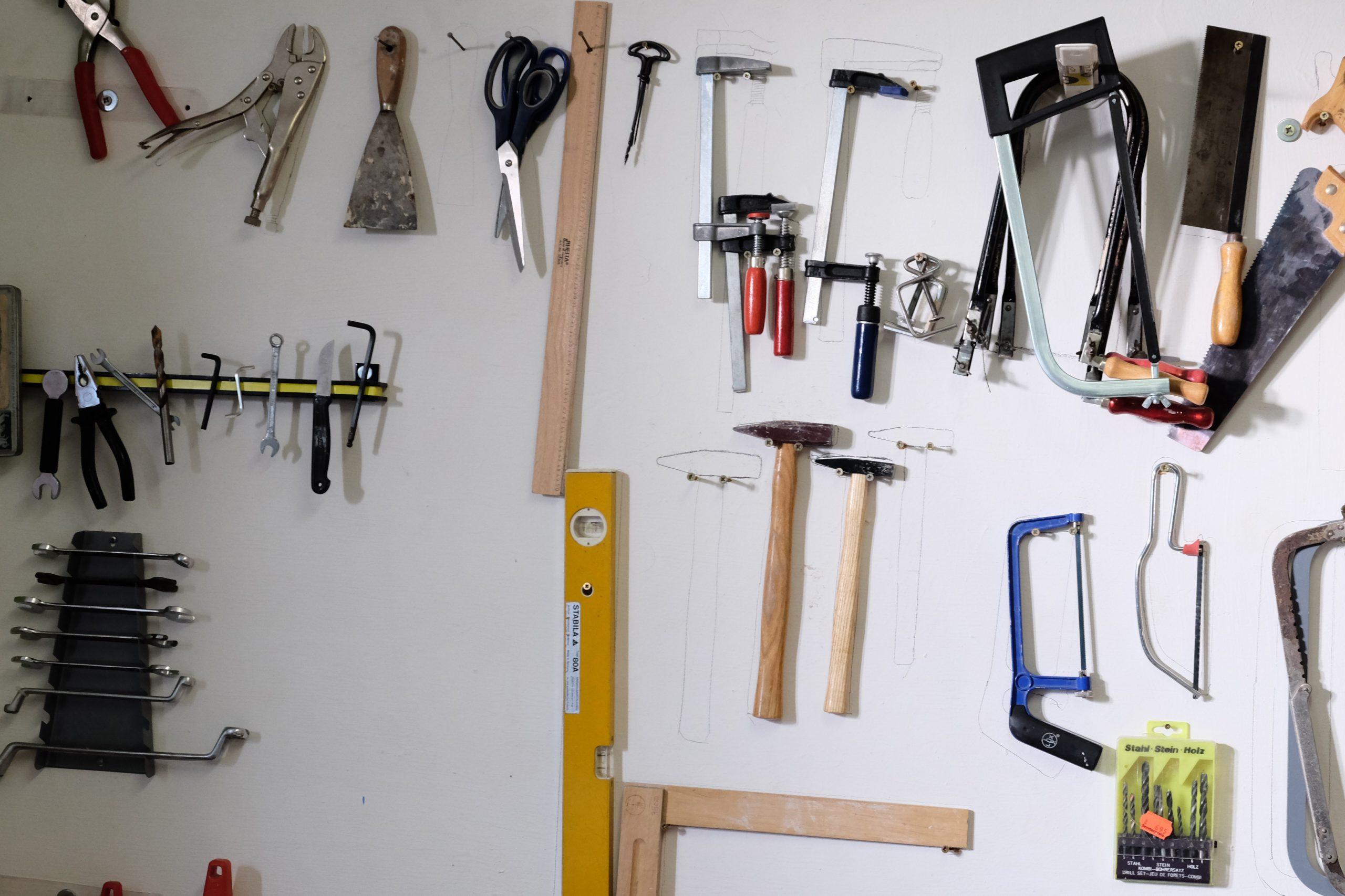 Weiße Wand mit einem darauf hängendem Werkzeug