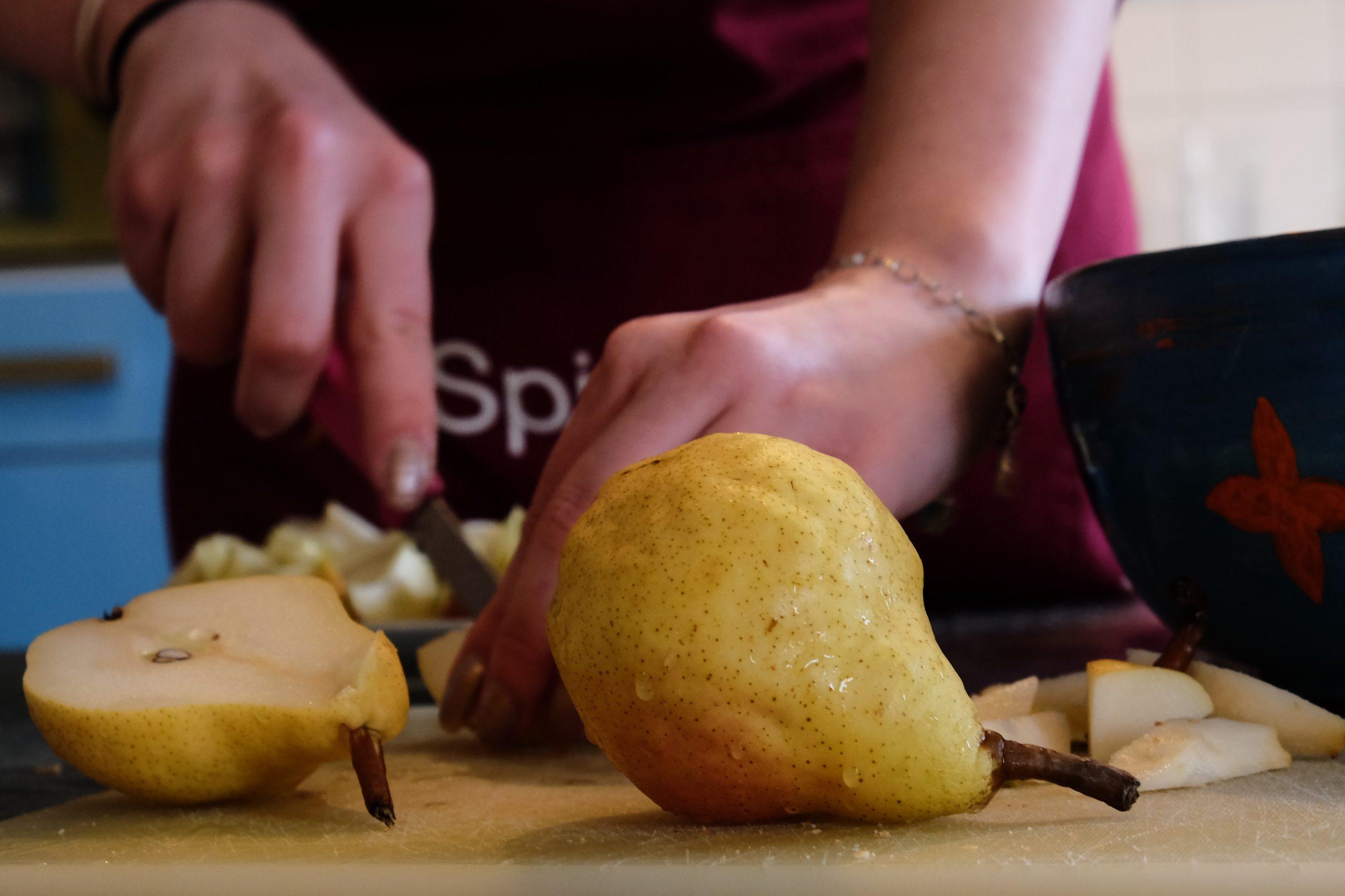 Eine Frau schneidet eine Birne auf