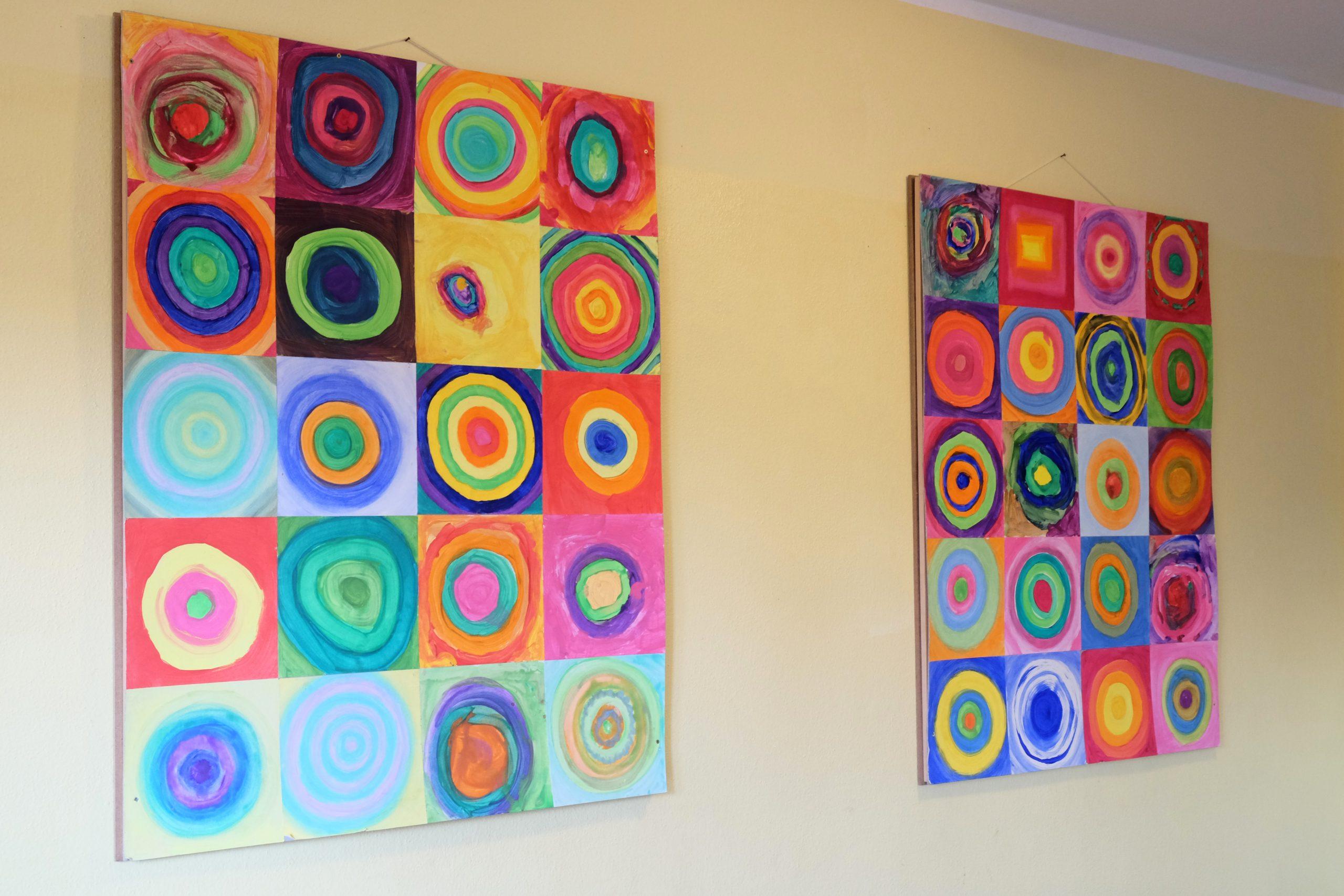 Farbenfrohe Kunstwerke hängen an der Wand