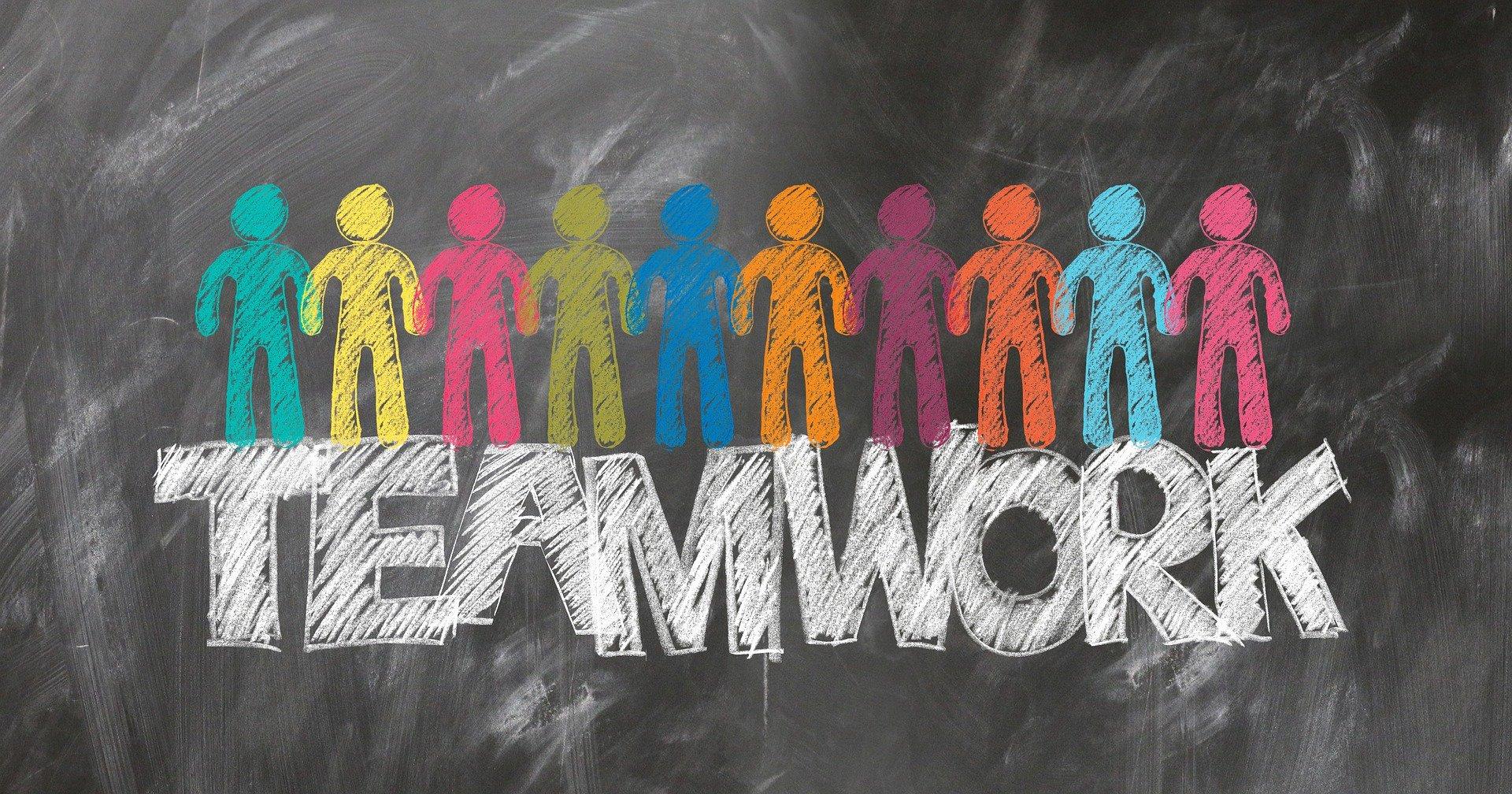 Schultafel mit Kreideschrift Teamwork und stilisierten bunten Menschen