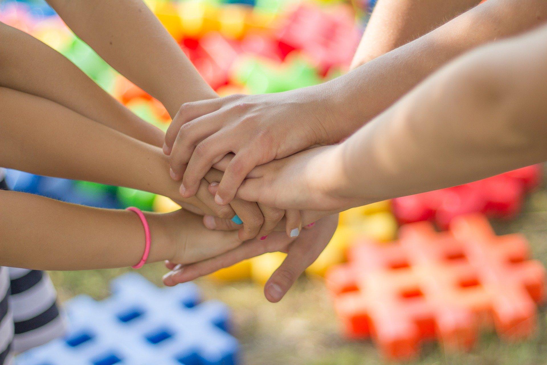 Hände von Kindern und Erwachsenen aufeinander
