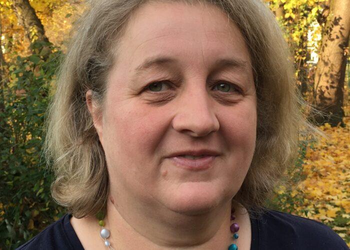 Porträtfoto Rosi Pösl mit Wald im Hintergrund